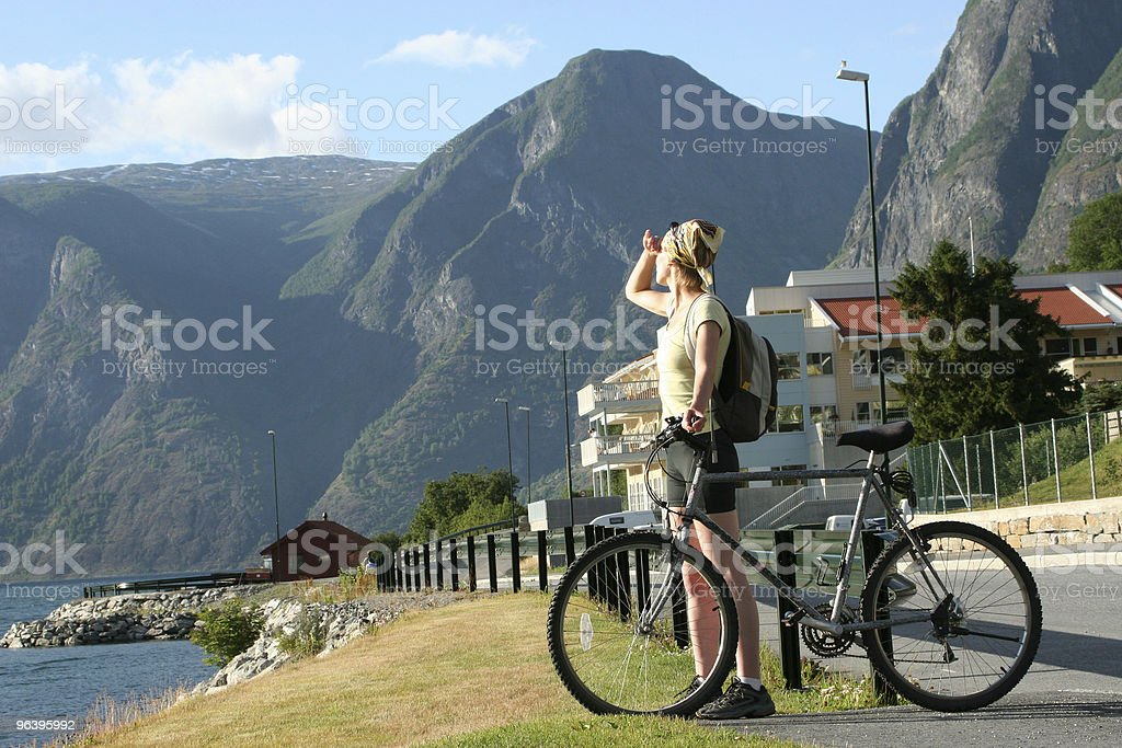 Adult woman with bike looking at the mountains 2 - Royalty-free Adult Stock Photo