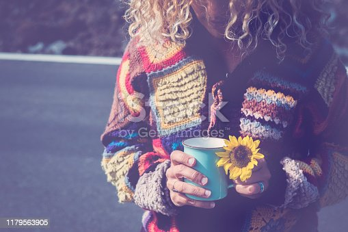adult woman with cup of coffee and yellow sun flower with road in backgrund - concept of travel and independence for free people outdoor