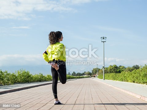 istock Adult Woman With Ponytail Warming Up For Sport 898412440