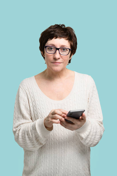 Adult woman with smartphone in hand looking at camera stock photo