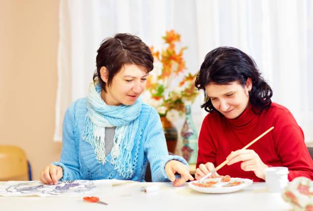 有特殊需要的成年女性從事手工技藝在康復中心 - 成年人 個照片及圖片檔