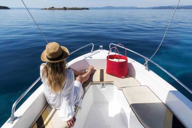 adult woman with white pareo and sitting on yacht while travelling in the sea, ouranoupoli, greece - yacht front view stock photos and pictures