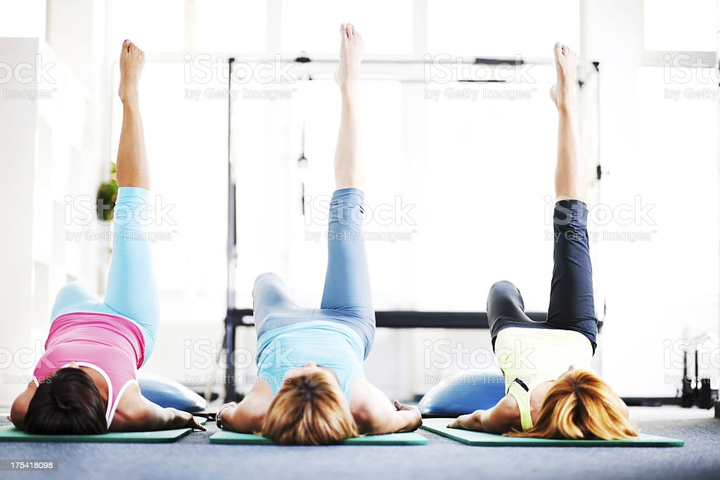 Adult women doing stretching exercises on Pilates class. stock photo
