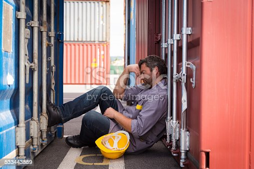 adult worker portrait in large container port, taking a nap in the shade