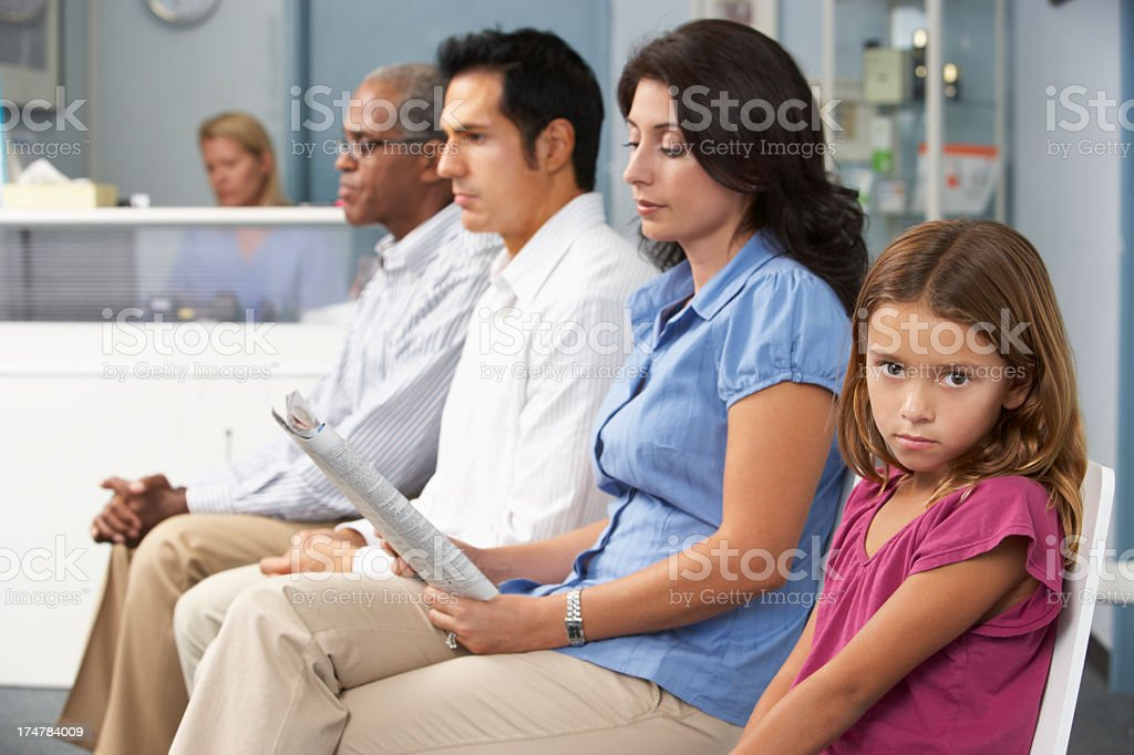 3 adults and 1 young girl sitting in a doctor's waiting room stock photo