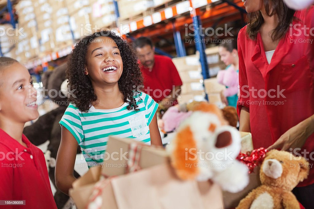 Adults and children donating toys at Christmas charity drive stock photo