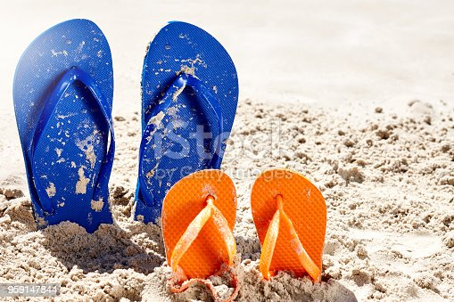 Two pairs of flip flops - one adult, one for a child, are stuck in the sand on a beach. Vacation time.