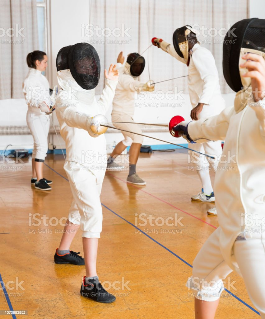 Adults and teens wearing fencing uniform practicing with foil stock photo