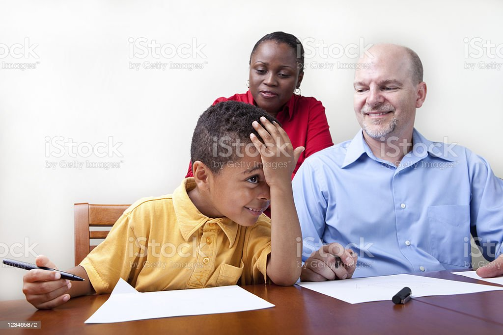 Adults attempting to help a child with his home work royalty-free stock photo