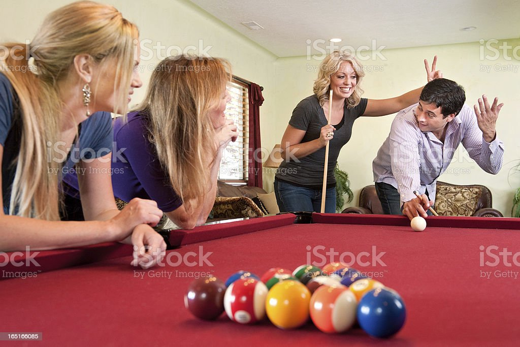 Adults having fun playing pool in home game room stock photo