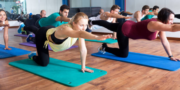 adults having yoga class in sport club - metodo pilates foto e immagini stock