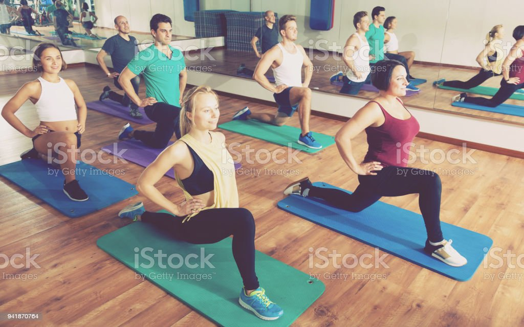 Adults having yoga class in sport club stock photo