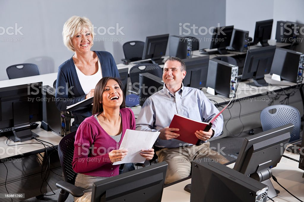 Adults laughing in computer lab stock photo