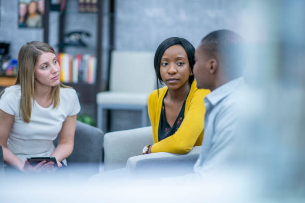 Adults listen attentively to each other in a group therapy session stock photo
