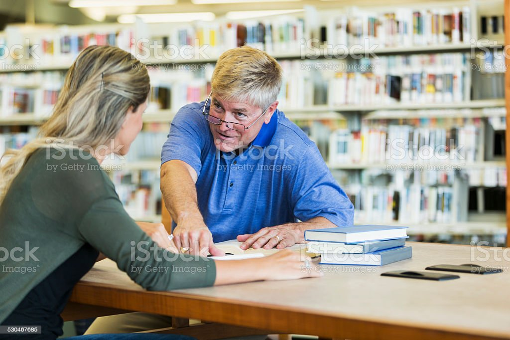 Adults studying in the library stock photo
