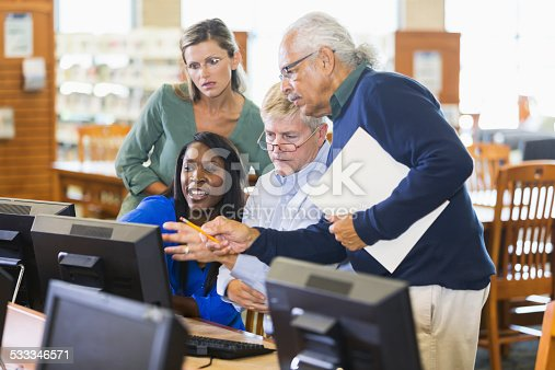 876965270 istock photo Adults studying on computers in library 533346571