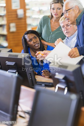 876965270 istock photo Adults studying on computers in library 534973711