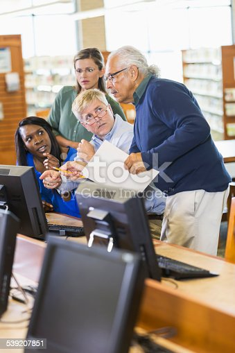 876965270 istock photo Adults studying on computers in library 539207851