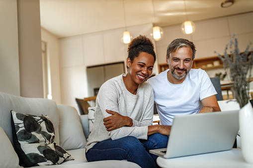 Two adults, smiling, browsing something online.