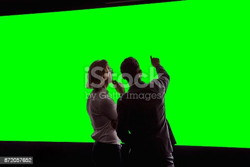 istock Adults Viewing a Large Green-Screen 872057652