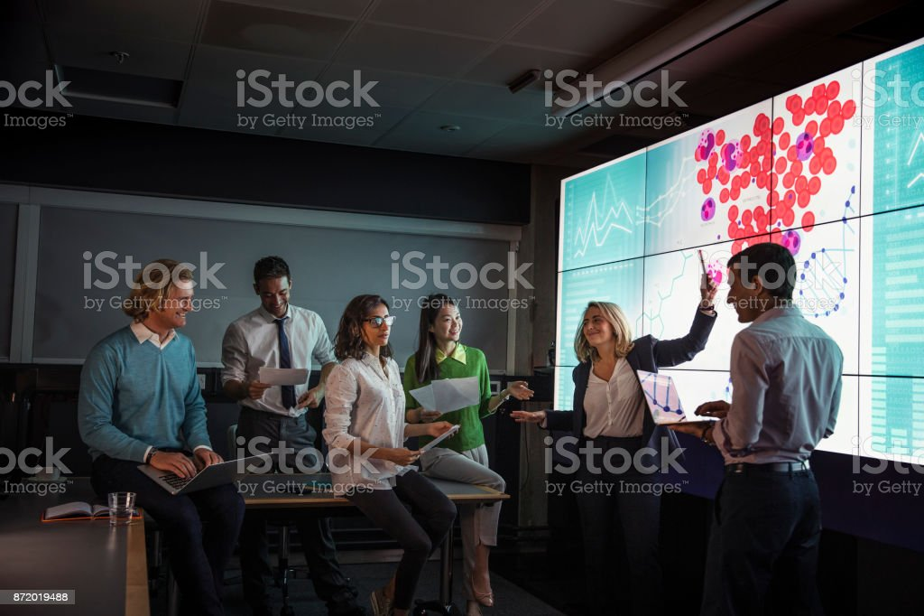 Adults Viewing Data on a Large Display Screen stock photo