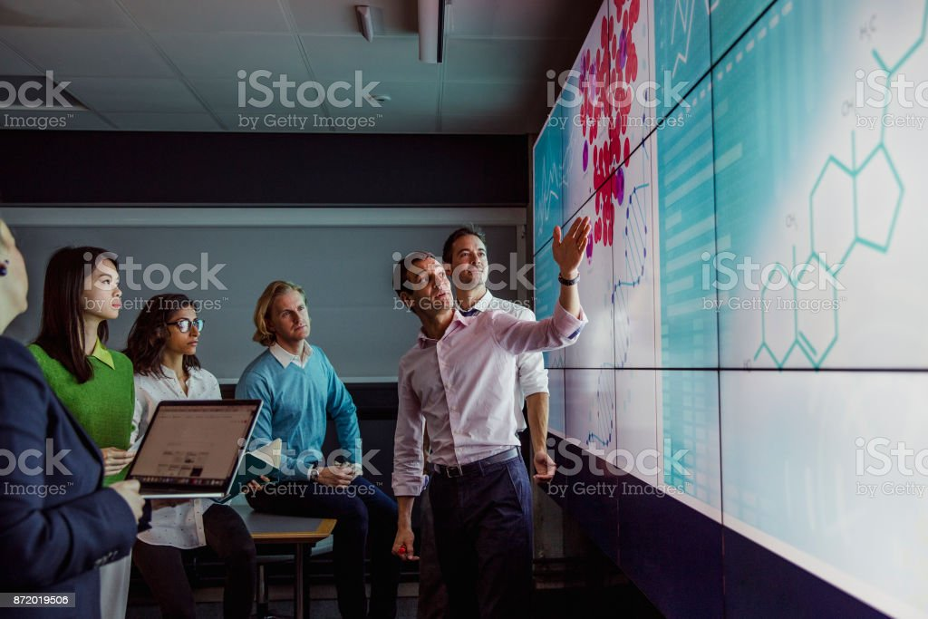 Adults Viewing Data on a Large Display Screen Group of business professionals in a dark room standing in front of a large data display screen with information. 30-39 Years Stock Photo