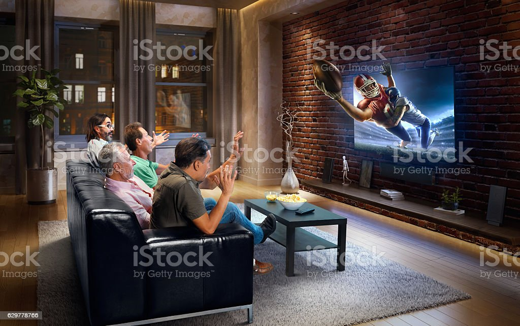 Adults watching American football game at home stock photo