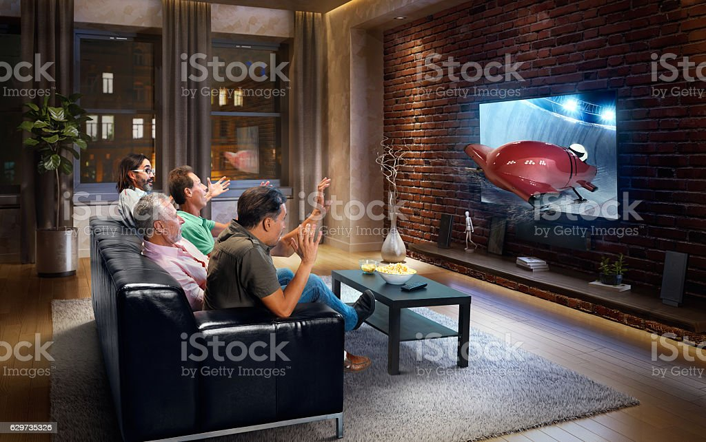 Adults watching Bobsleigh race at home stock photo