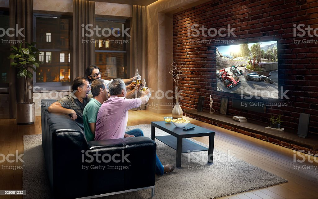 Adults watching Car sprint at home stock photo