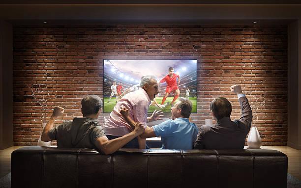adults watching soccer game at home - fußball themenzimmer stock-fotos und bilder