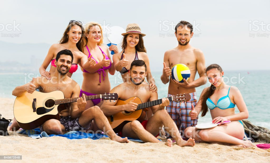 Adults with guitar at beach stock photo