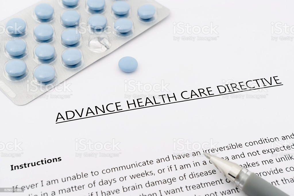 advance health care directive with blue pills ans grey pen stock photo
