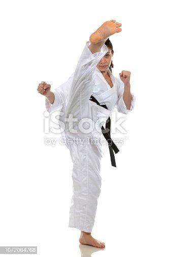 Martial artist kicking high above head.