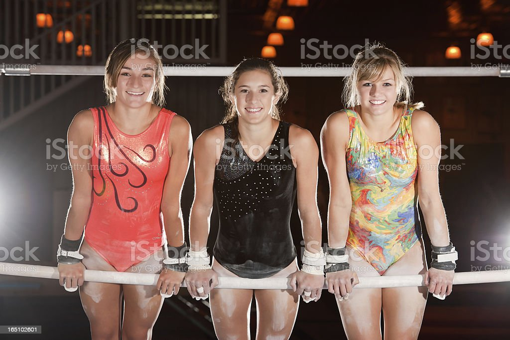 Advanced Gymnasts Pose On Uneven Bars stock photo