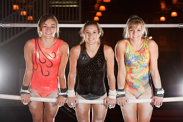 advanced gymnasts pose on uneven bars - uneven parallel bars stock photos and pictures