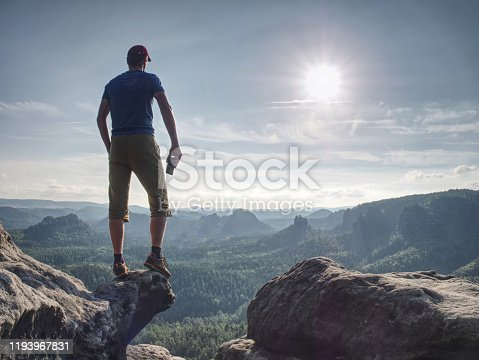 Advanture man in shorts and blue singlet watching down. Traveler on cliff mountains over  great Canyon.