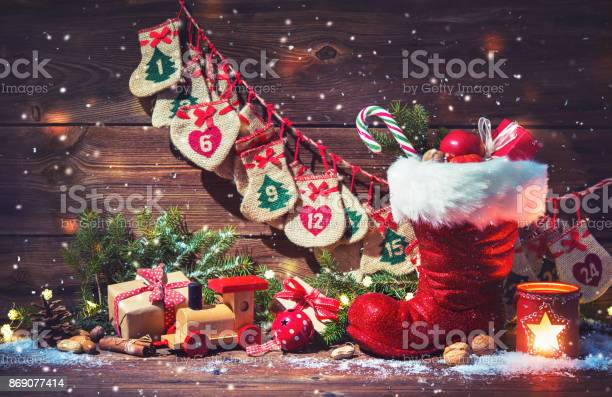 Advent calendar and santas shoe with gifts on rustic wooden picture id869077414?b=1&k=6&m=869077414&s=612x612&h=3hbz2jsmvwcio2t2euncezkwekz9fmvnj93 cp2f8ti=