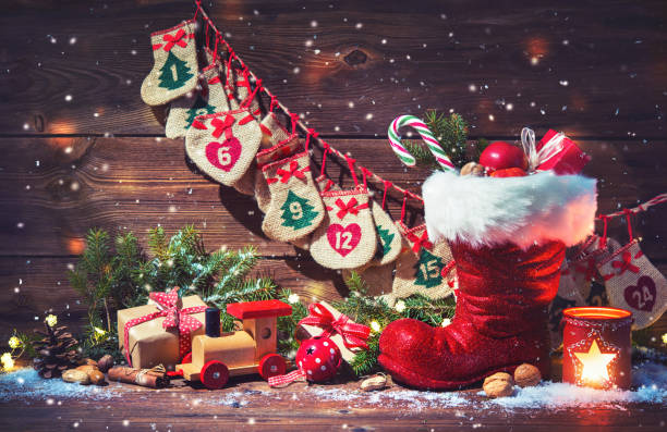 Advent calendar and Santa's shoe with gifts on rustic wooden background stock photo