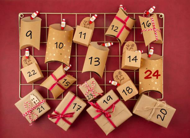 calendrier de l'avent avec des boîtes en carton d'artisanat sur le panneau de maille - calendrier de l'avent photos et images de collection