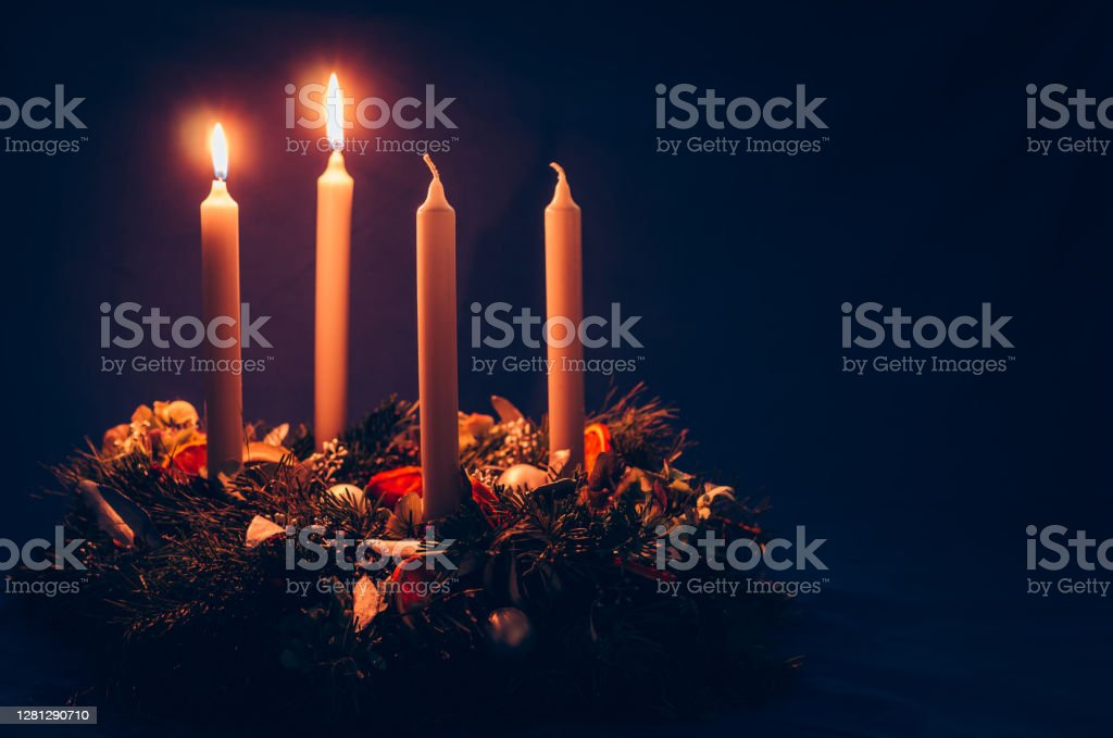 2. advent candle burning on advent wreath 4 candle advent wreath on black background copy space Advent Stock Photo