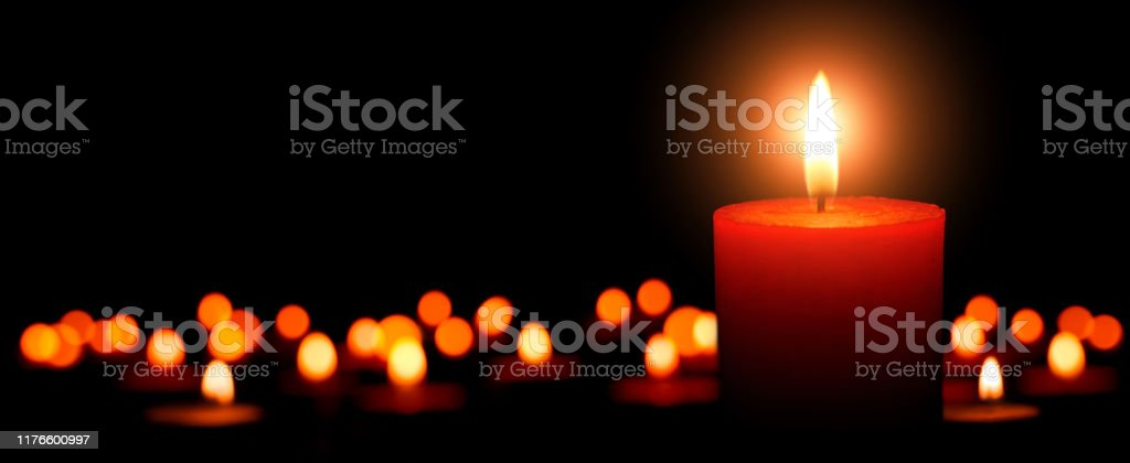Low-key studio shot of elegant advent candles with one flame in the...