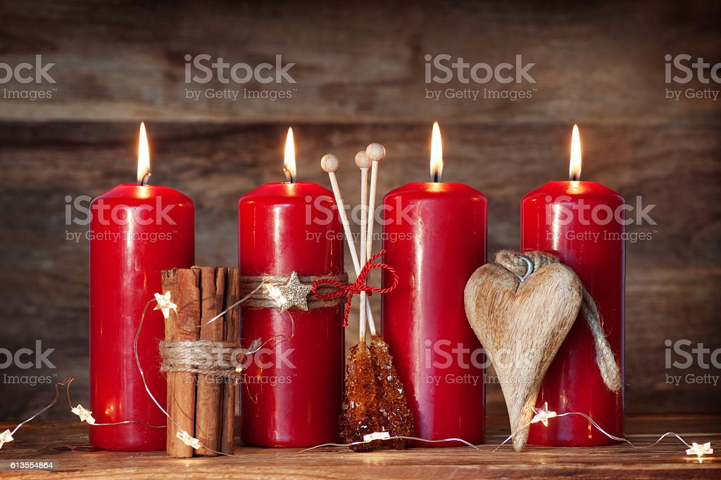 Advent candles with cinnamon and candy in front of a wooden Background