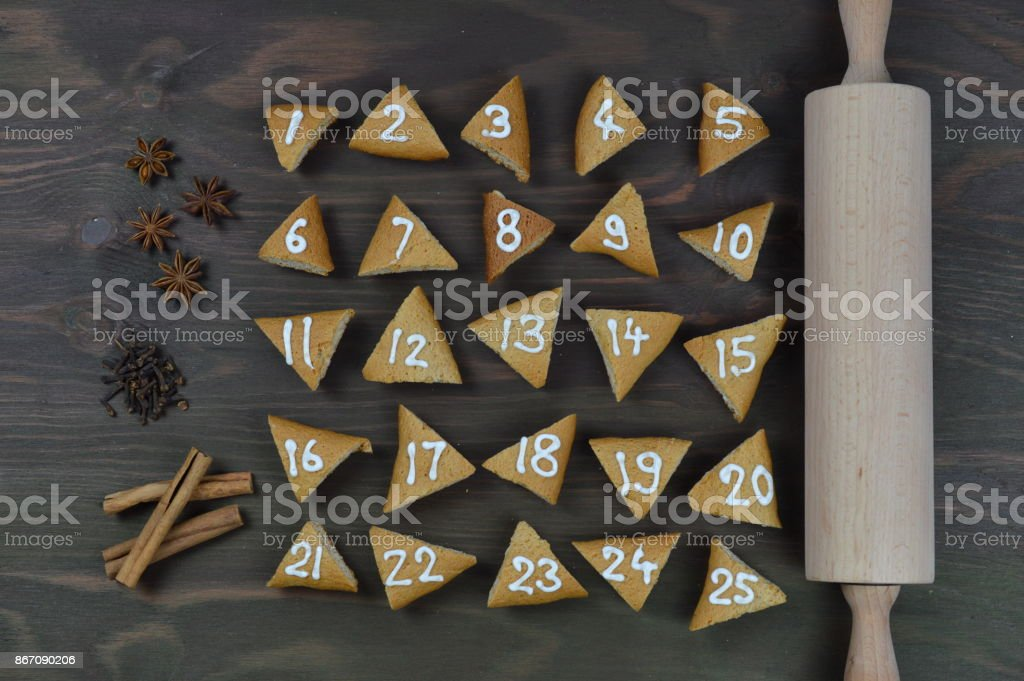 25 advent cookies on brown wood with rolling pin and spices stock photo
