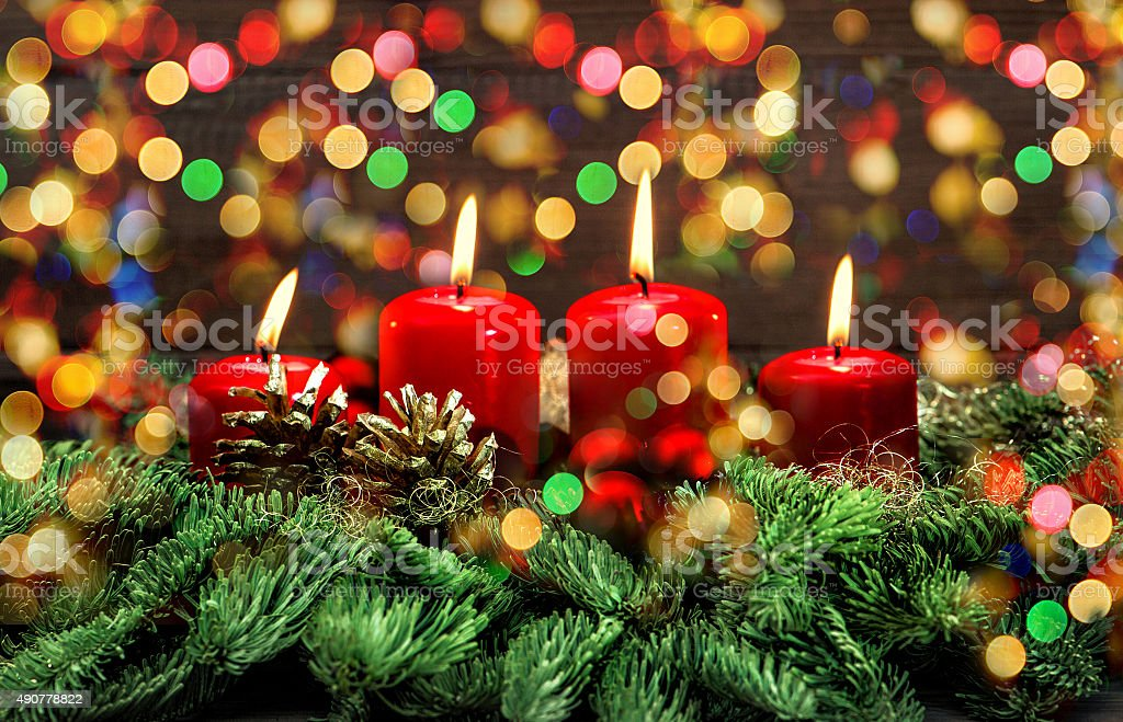 Advent decoration with burning candles and colorful lights stock photo