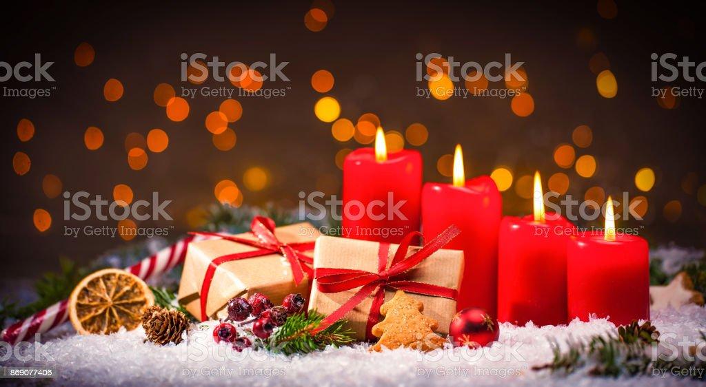 Decoración de Adviento con cuatro velas ardiendo y cajas de regalo - foto de stock