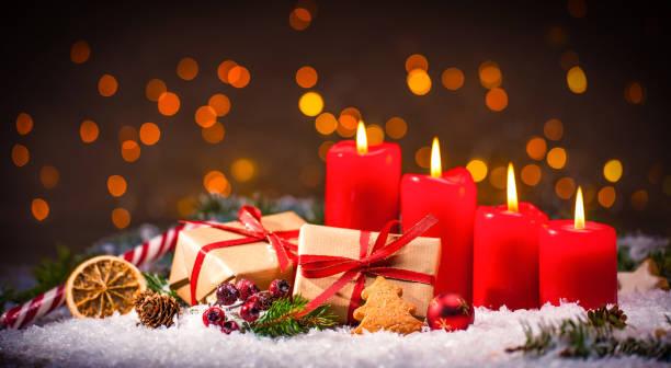 decoración de adviento con cuatro velas ardiendo y cajas de regalo - adviento fotografías e imágenes de stock