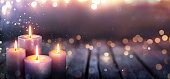 Abstract Advent - Four Purple Candles With Bokeh Lights On wooden Table