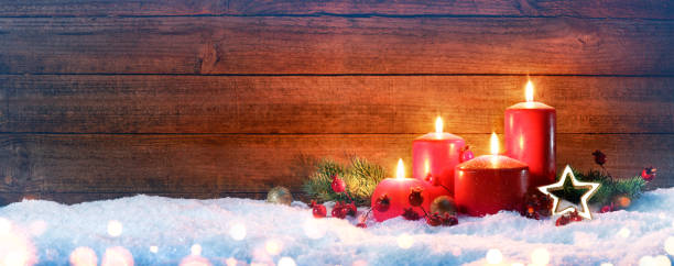 Advent Red Candles On Snow With Vintage Wood stock photo