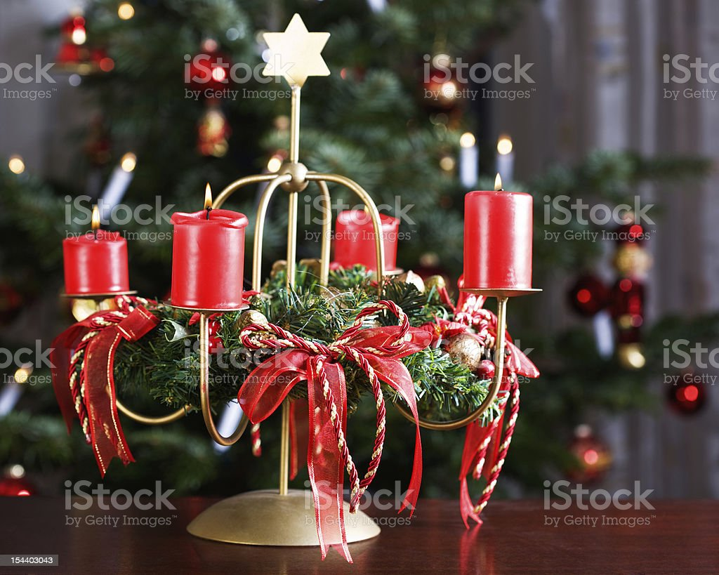 Advent wreath with four burning red candles, Christmas tree on...