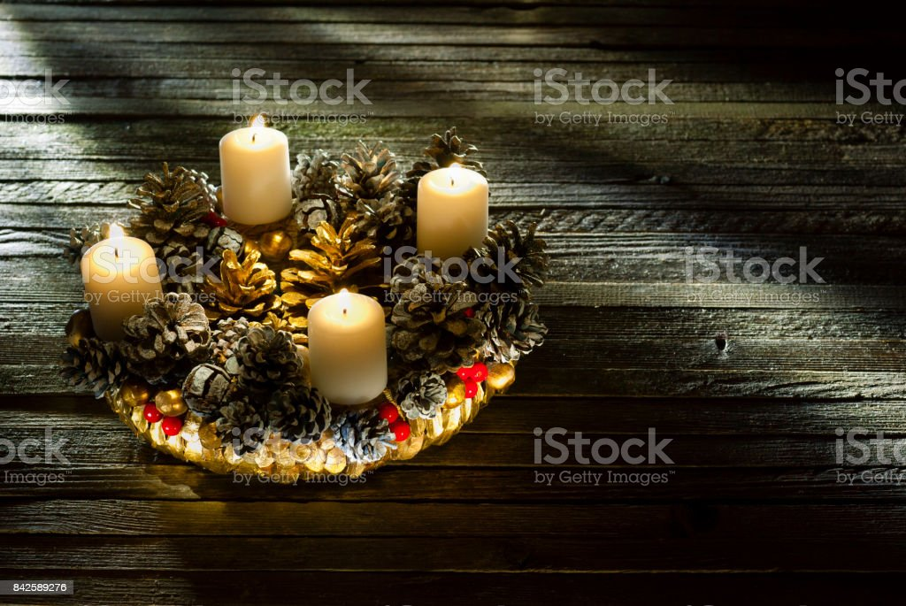 advent wreath with four burning candles on old wooden table background